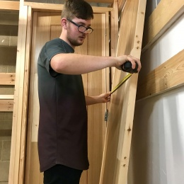 A City College student measuring up an Elliotts door